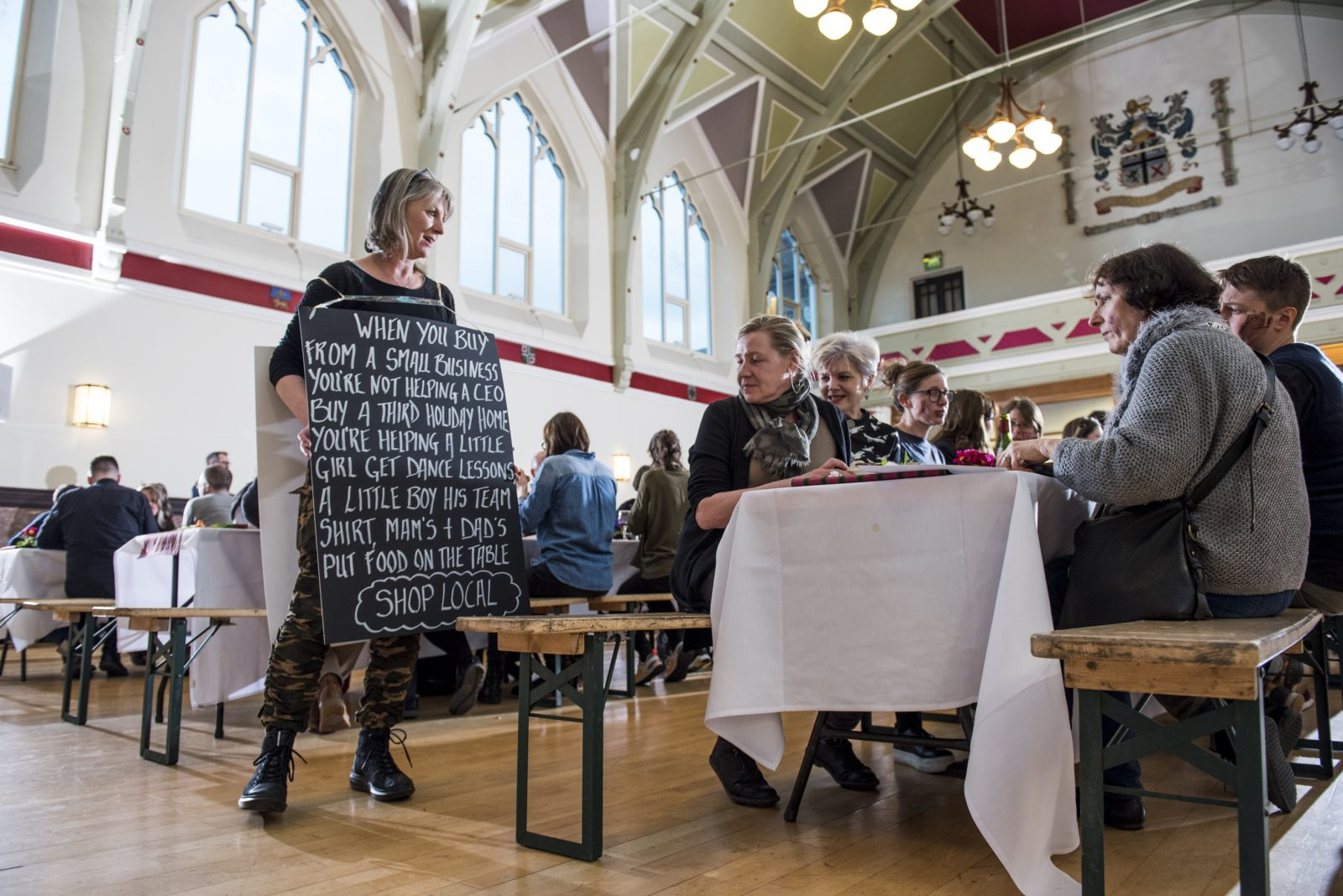 A person in camouflage trousers and black boots is wearing a blackboard sandwich board and standing at the end of a table. The blackboard reads 'When you buy from a small business you're not helping a CEO buy a third holiday home you're helping a little girl get dance lessons, a little boy his team shirt, Mam's and Dad's put food on the table. Shop Local.' There are people sat at the table reading the blackboard.