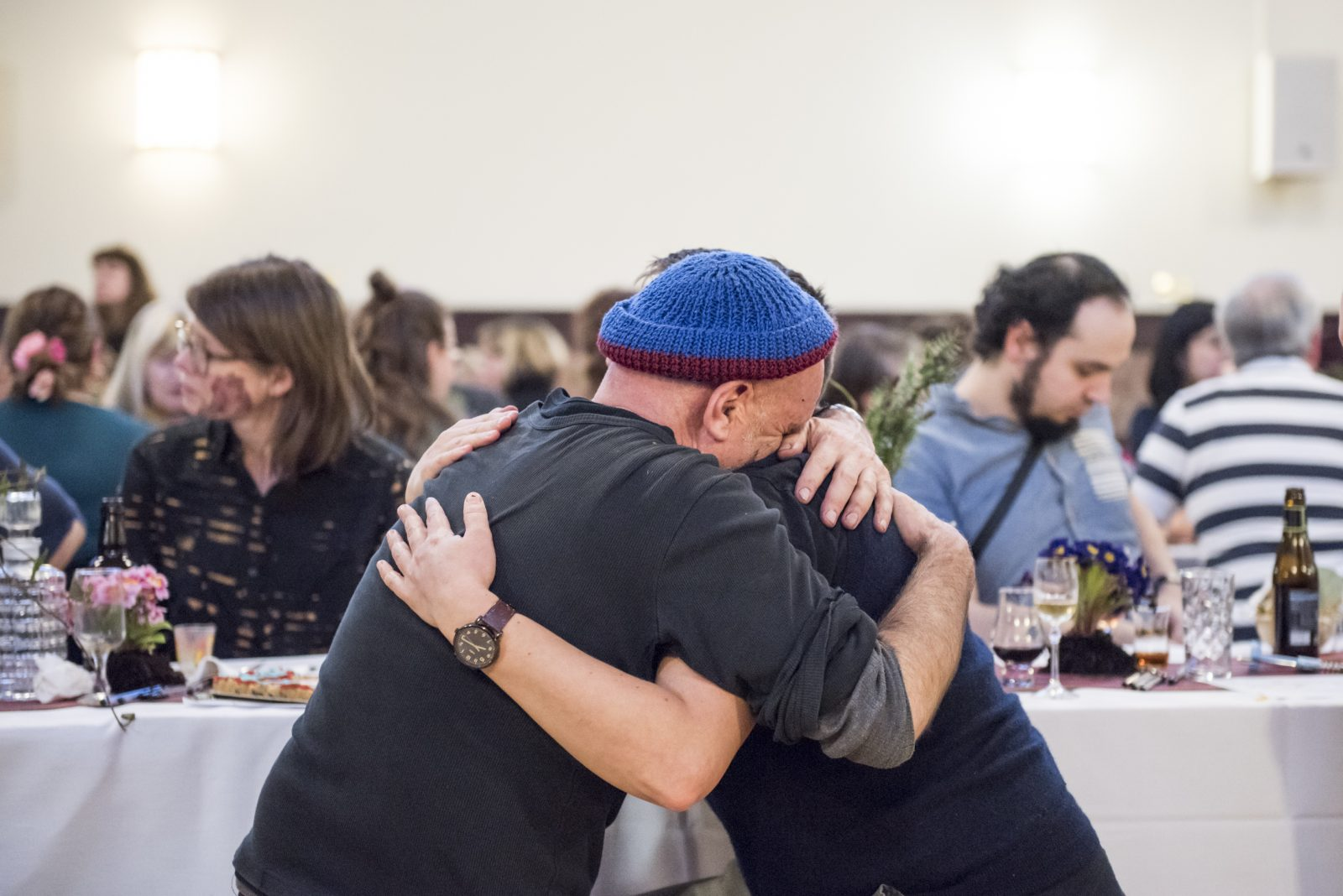 Two people sitting at a table hug intensely. One wears a blue hat and buries their head in the shoulder of the other. Behind them the room is full of people sitting at long tables.